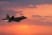 F-22 Fighter Jet flying with afterburner at sunset