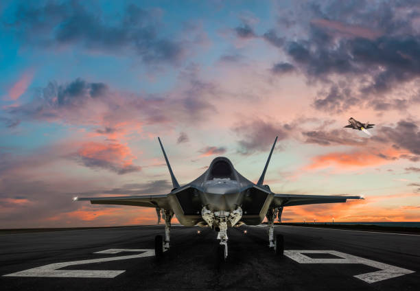 F-35 fighter jet ready to takeoff on runway at sunset stock photo