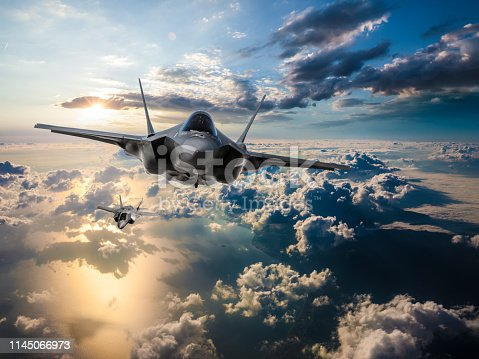 1145066973 istock photo F-35 Fighter Jets flying over the clouds at sunset 1145066973