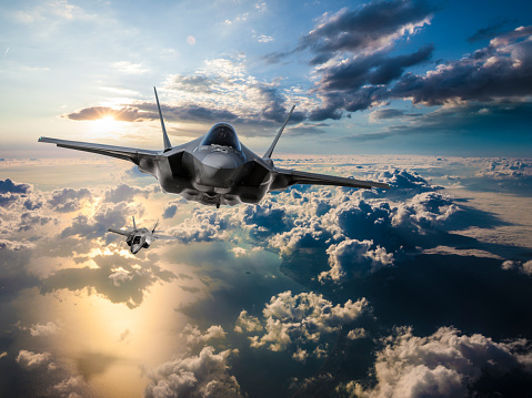 istock F-35 Fighter Jets flying over the clouds at sunset 1145066973