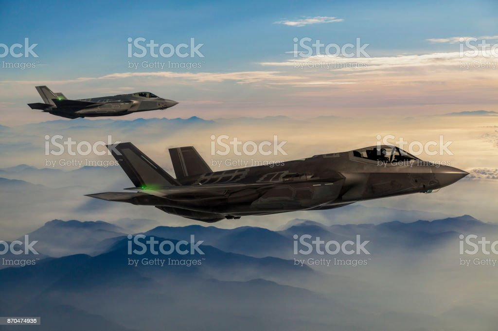 Fighter Jets flying over the fogy mountains at dusk stock photo