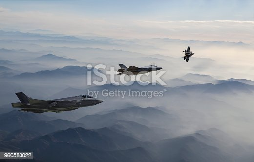 1145066973 istock photo Fighter Jets flying over the misty mountains at dusk 960580022