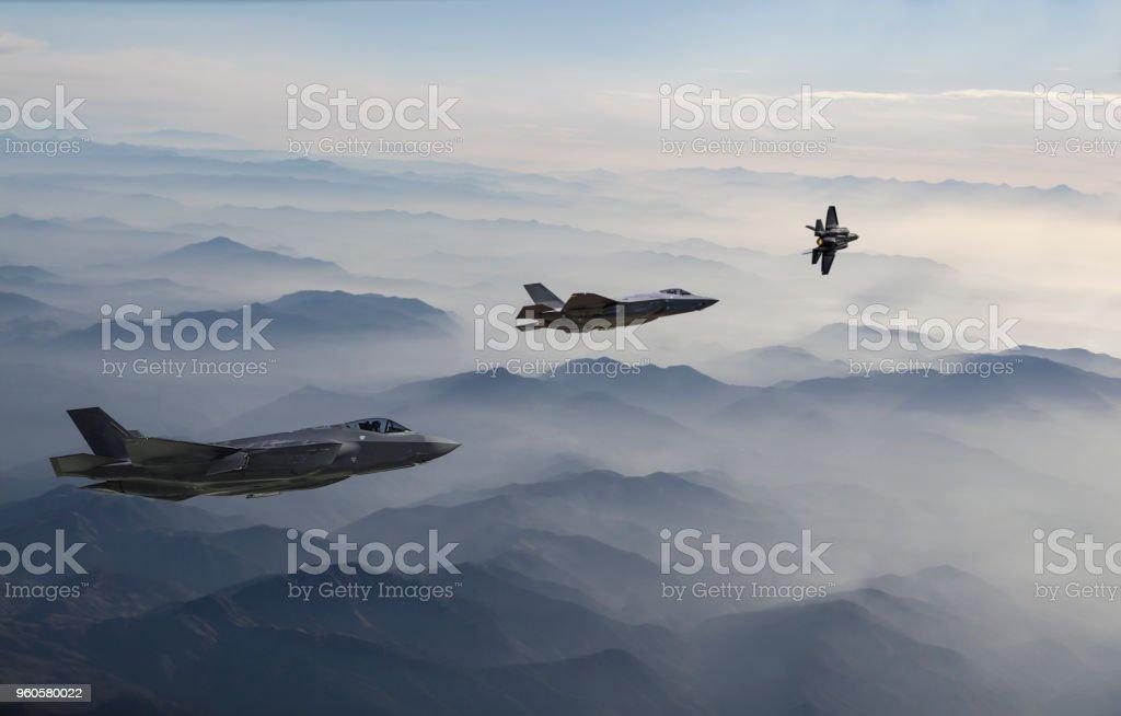 Aviones de combate sobrevolando las montañas nubladas al atardecer - foto de stock