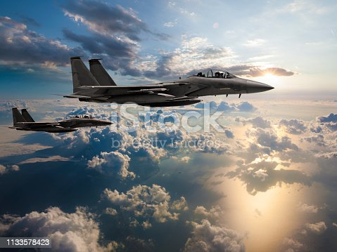 Fighter Jets flying over the ocean at sunset