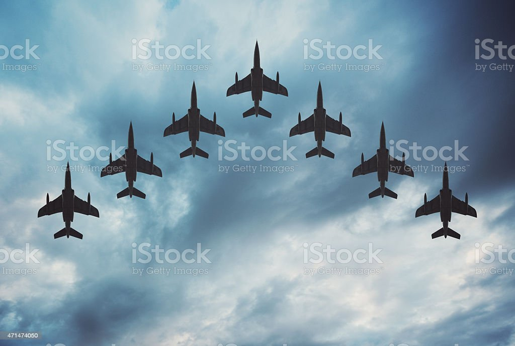 Fighter Jets in Formation Fighter jets arranged in a V shaped flying formation under dramatic overcast skies.  Composite image. 2015 Stock Photo