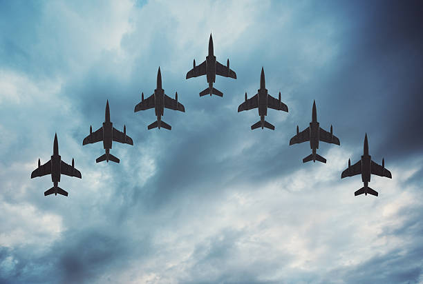 Fighter Jets in Formation Fighter jets arranged in a V shaped flying formation under dramatic overcast skies.  Composite image. aerodynamic stock pictures, royalty-free photos & images