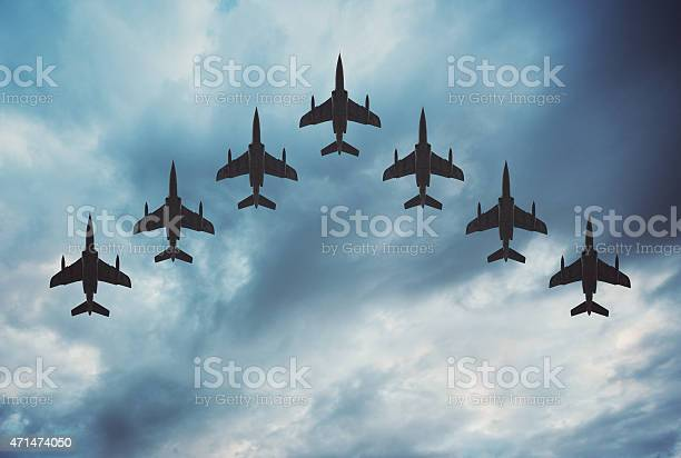 Fighter jets arranged in a V shaped flying formation under dramatic overcast skies.  Composite image.