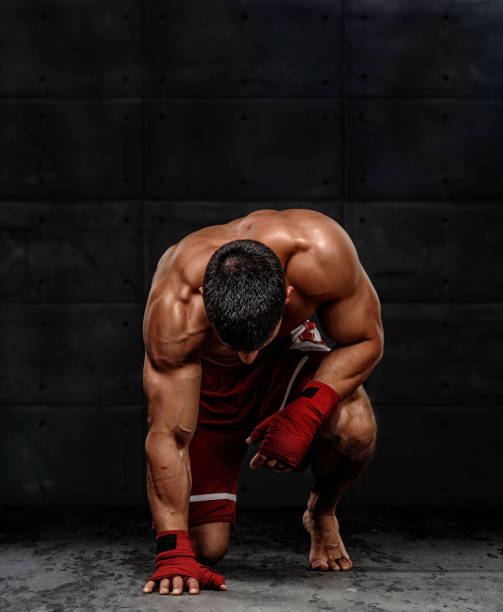MMA Fighter Kneeling on the Floor Before the Fight stock photo