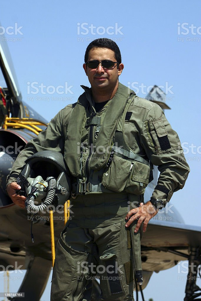 Fighter Pilot A full equiped fighter pilot stands in front of a fighter! Aggression Stock Photo