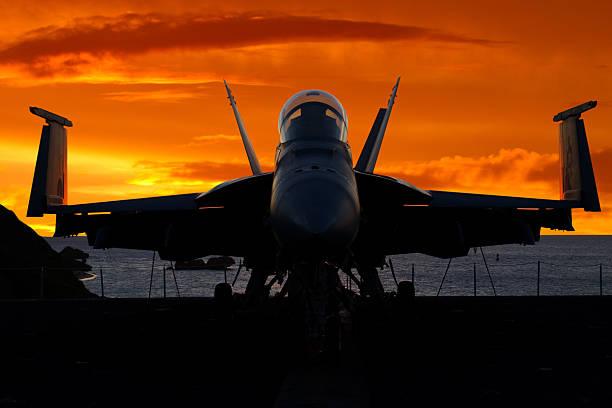 jagdflugzeug bei sonnenaufgang - flugzeugträger stock-fotos und bilder
