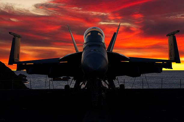 jagdflugzeug bei sonnenuntergang - flugzeugträger stock-fotos und bilder