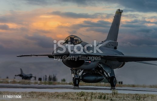 F-16 fighter plane ready to takeoff on runway at sunset
