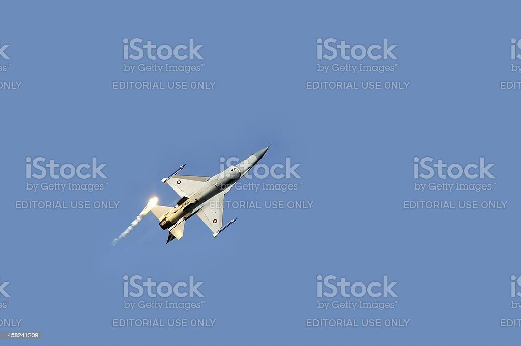 F16 fighter plane releasing infrared countermeasure decoy stock photo