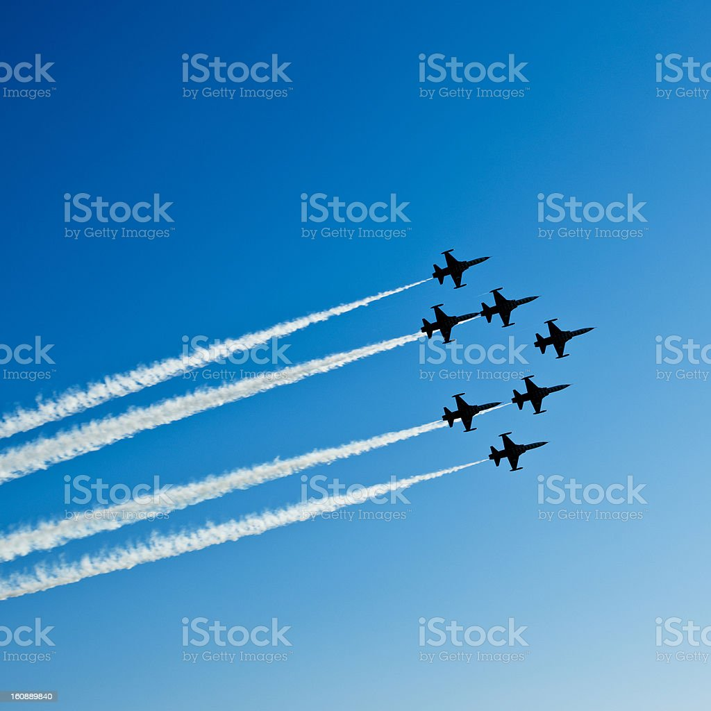 Fighter planes in airshow on blue sky Square composition of seven fighter planes with smoke in airshow. Clear blue sky with copy space. Image taken with Hasselblad H3D Camera System and developed from RAW. Activity Stock Photo
