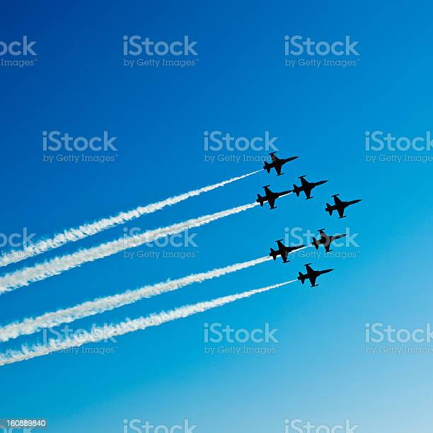 Square composition of seven fighter planes with smoke in airshow. Clear blue sky with copy space. Image taken with Hasselblad H3D Camera System and developed from RAW.