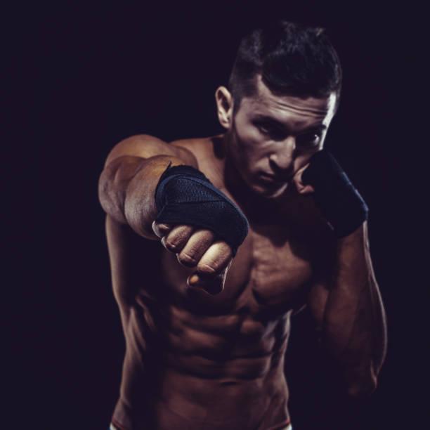 MMA Fighter Preparing Bandages For Training. Dark background - foto de acervo