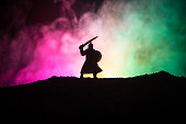 Fighter with a sword silhouette a sky. Medieval knight with sword. Selective focus