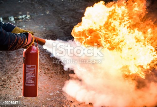 A man using a carbon dioxide fire extinguisher to fight a fire.
