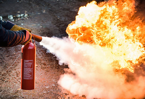 Fighting a fire A man using a carbon dioxide fire extinguisher to fight a fire. extinguishing stock pictures, royalty-free photos & images