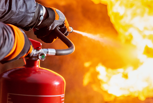 Close-up as a firefighter uses a fire extinguisher to spray water at the base of the flames of a fire.