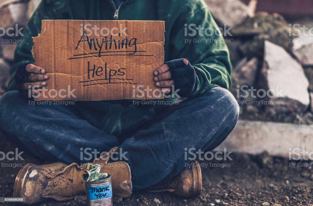 Fighting adversity. Homeless man with sign and money tin stock photo