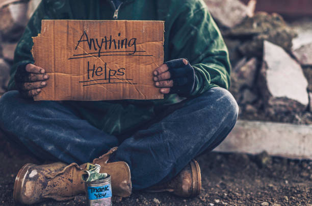 fighting adversity. homeless man with sign and money tin - poverty stock pictures, royalty-free photos & images