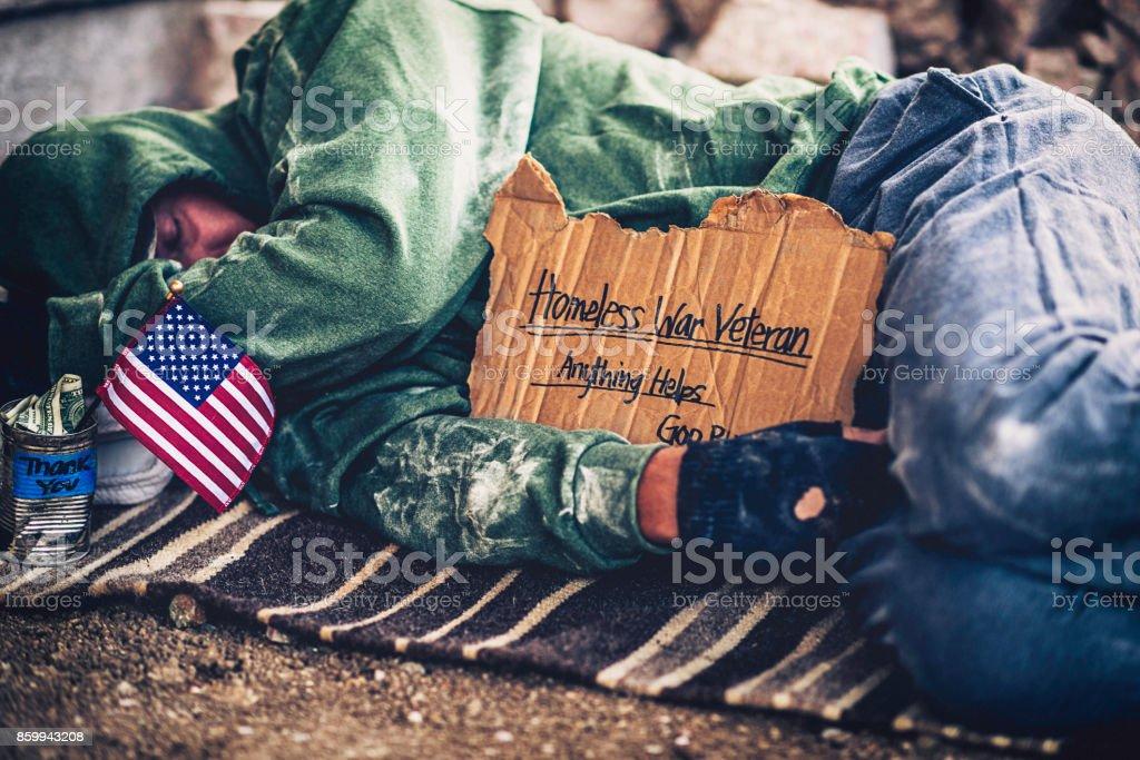 Fighting adversity. Homeless war veteran sleeping with sign and money tin stock photo