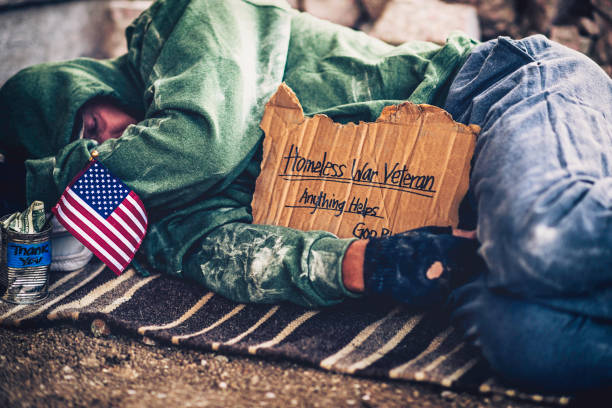 fighting adversity. homeless war veteran sleeping with sign and money tin - homelessness stock photos and pictures