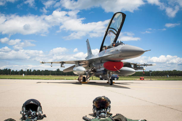 F-16 Fighting Falcon fighter jet helmets GEILENKIRCHEN, GERMANY - JUNE 17, 2007: F-16 Fighting Falcon fighter jet plane with pilot helmets in front on the tarmac. f 16 fighting falcon stock pictures, royalty-free photos & images
