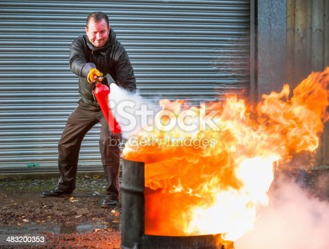 A man using a carbon dioxide extinguisher to fight a fire.