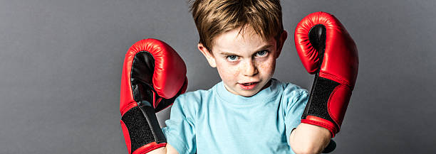 fighting kid with freckles showing his boxing gloves up stock photo