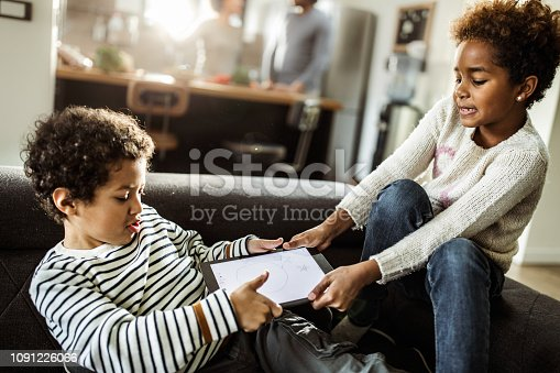 Small black siblings fighting over digital tablet in the living room.