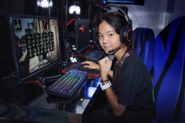 fighting young girl playing computer games in internet cafe - esports stock photos and pictures