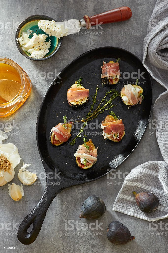 Figs and cheese wrapped in meat on a pan stock photo