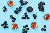 Figs and grapes on blue background flat lay