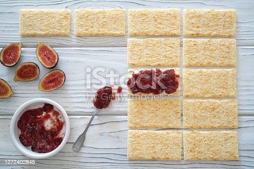 Figs jam homemade with fig fruits, cheese, nuts and bread toast slice on white rustic wooden background