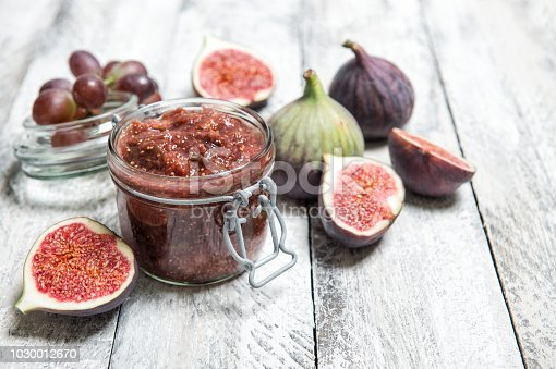Figs jam in jar. Fruit marmalade on rustic wooden background