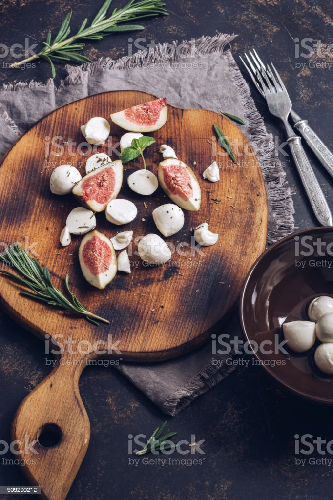 Figs of figs and mozzarella cheese on a cutting board. Mediterranean food. Selective focus stock photo