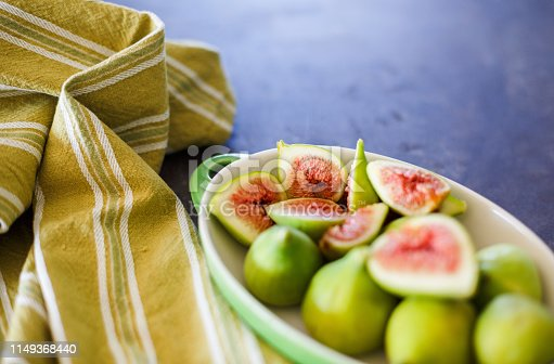Whole and chopped green fresh figs in the plate served on the table.