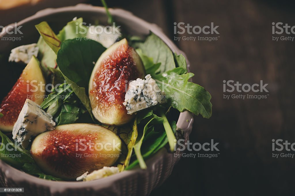 figs salad with blue cheese and ruccola on wooden background stock photo