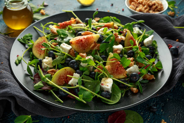 figs salad with blueberries, walnuts, feta cheese and green vegetables. healthy food - fig salad imagens e fotografias de stock