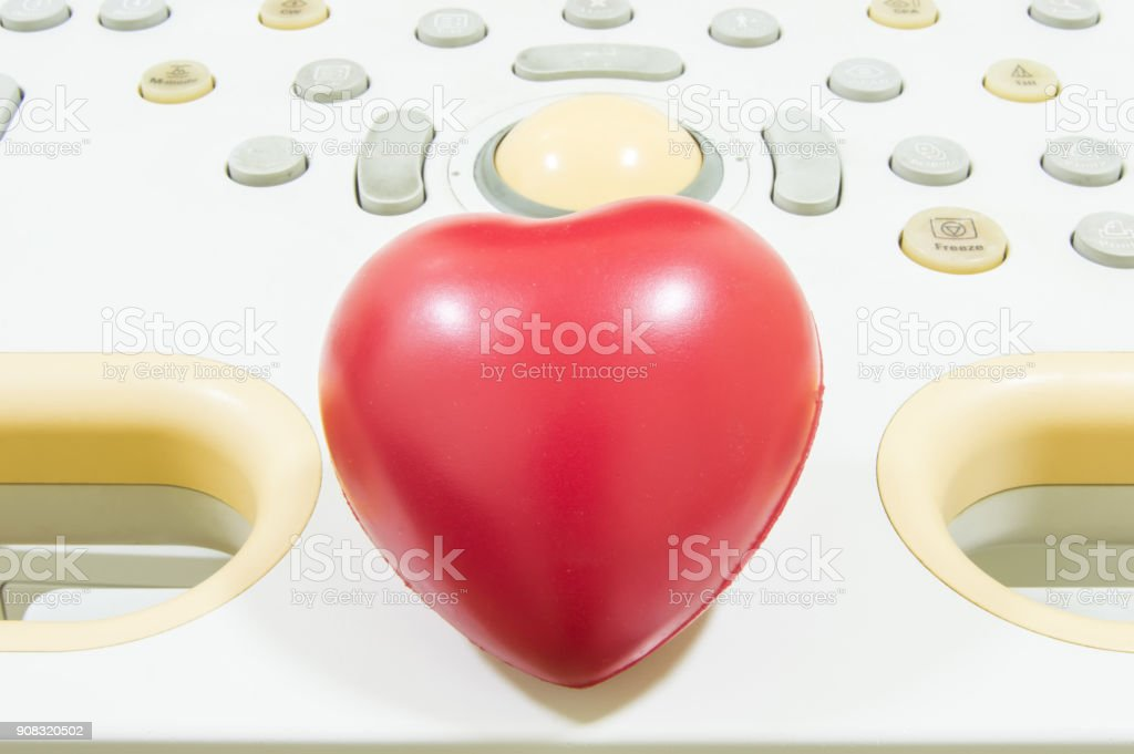 Figure heart is located on the remote control or keyboard of ultrasound machine. Concept photo for ultrasound cardiodiagnostics or heart conditions diagnosis in children and adults stock photo