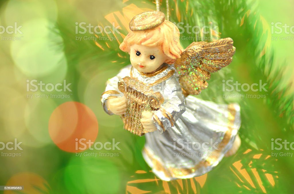 figure of little angel playing the harp against bokeh background stock photo