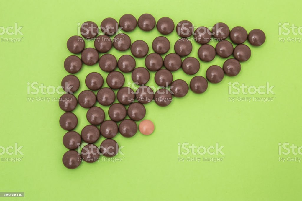 Figure or shape (contour) of human liver, composed of brown pills or tablets, with the gallbladder on a green background. The idea for the medical direction of Gastroenterology and Hepatology stock photo