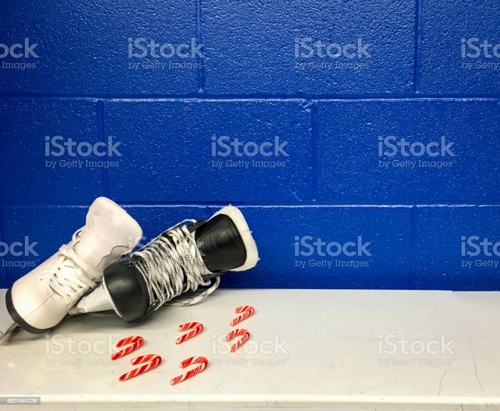 Figure skate and hockey skate with candy canes in locker room stock photo