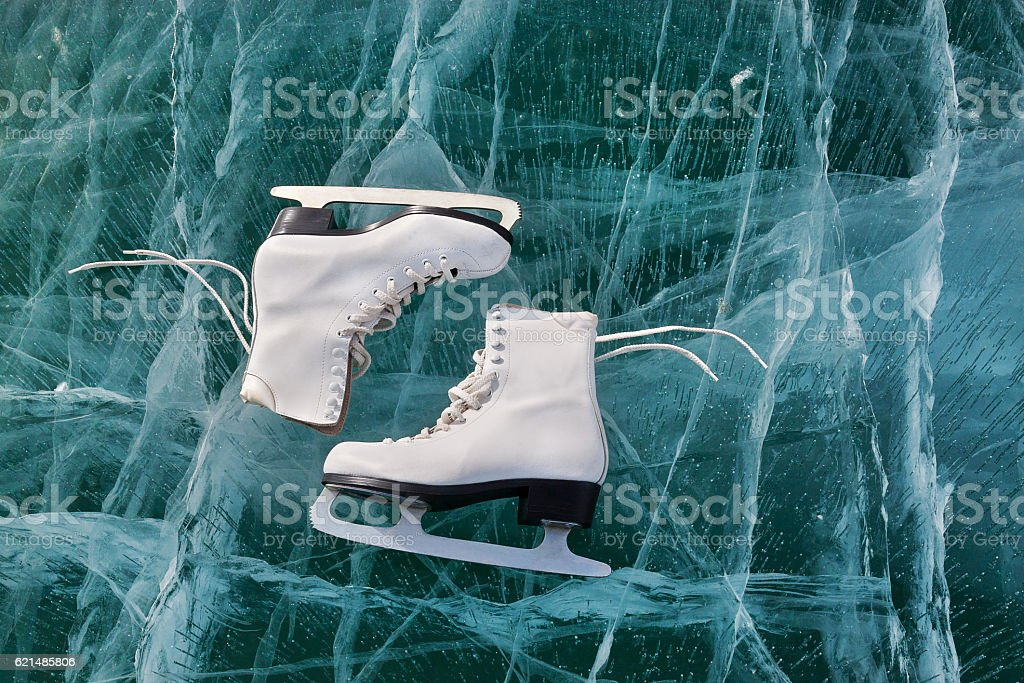 Figure skates at cracked ice surface. Winter sport concept Lizenzfreies stock-foto