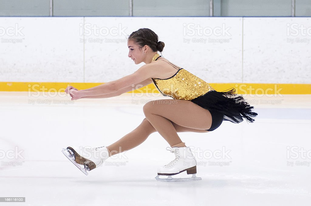Figure skating bending down to do a spin with leg stretched stock photo