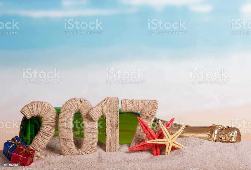 Figures 2017, bottle champagne, stars, gifts in sand against sea. photo libre de droits
