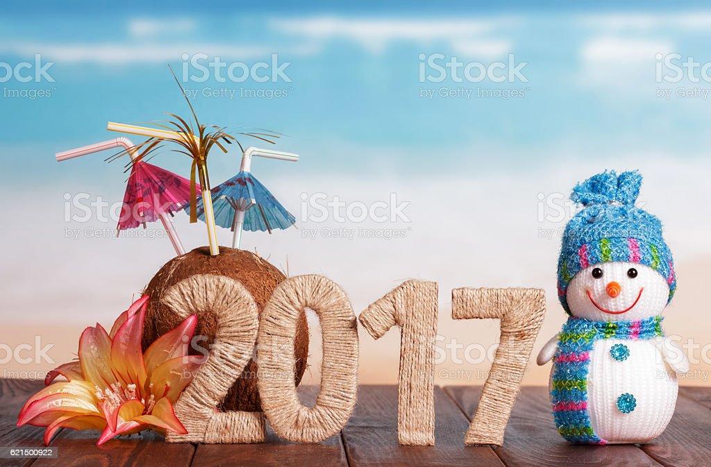 Figures 2017 coconut snowman and flower on table against sea. Lizenzfreies stock-foto