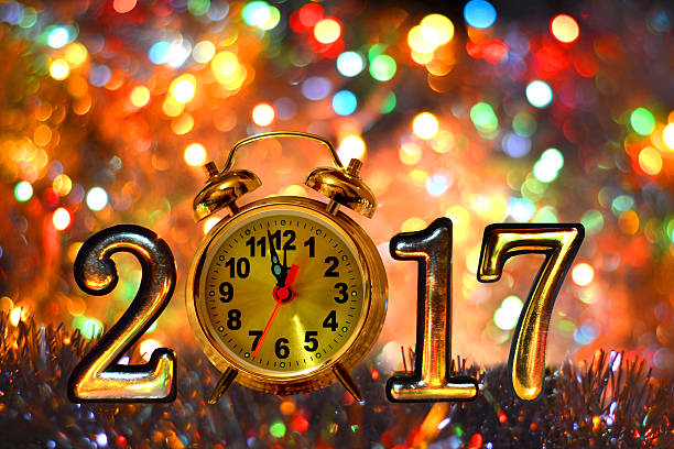 Figures 2017  on bright background of holiday lights Figures 2017 and clock (new year ,Christmas) on bright background of holiday lights. 12 17 months stock pictures, royalty-free photos & images